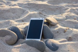 cellphone-on-the-beach-employees-who-cant-disconnect-sundance-vacations-the-benefit-of-travel-in-the-workplace